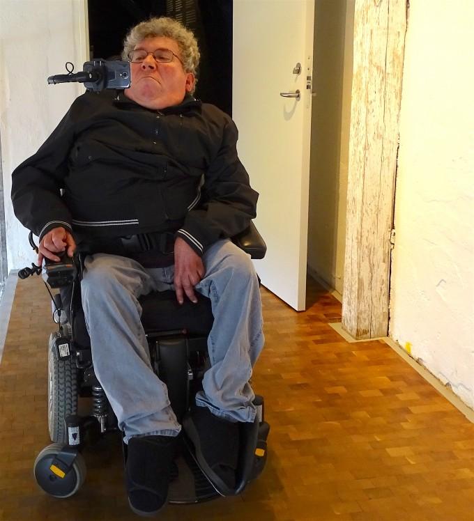 Sidder i kørestol med mobil i holder og styrer mobiltelefon med kørestolens joystick.