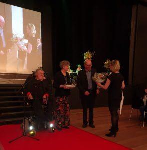 Overrækkelse af Handicapprisen 2019. Carsten Hansen og Merete Thaaning er på vegne af Østagergård ved at få overrakt blomster og en gave, der følger med prisen.