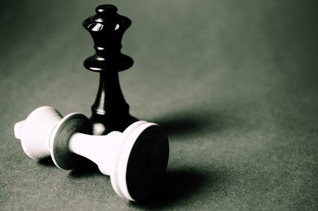 Et foto af to skakbrikker, hvor hvid konge er tumlet omkuld og sat ud af spillet.